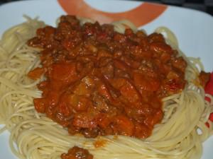 Voeg 3 eetlepels van het spaghetti kookwater toe aan de bolognesesaus.