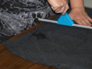 Leg de pullover op een tafel. Trek hem recht en plooivrij. Zorg voor een beetje spanning op de te behandelende plek. Neem vervolgens de raamtrekker en trek over de stof.