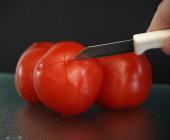 Snij met het mesje een kruis van een centimeter in de bolle kant (onderkant) van de tomaat.