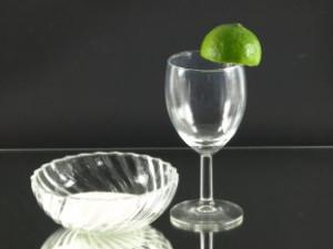 Het maken van het suikerrandje begint met het vochtig maken van de rand van het (cocktail)glas.