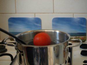 Het blancheren van een tomaat met het doel de omringede huid te verwijderen